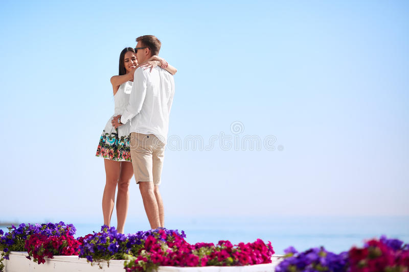 Cute lovers on a blue ocean background. Happy relationship. A romantic couple on a honeymoon. Romance and dating. Copy stock photos