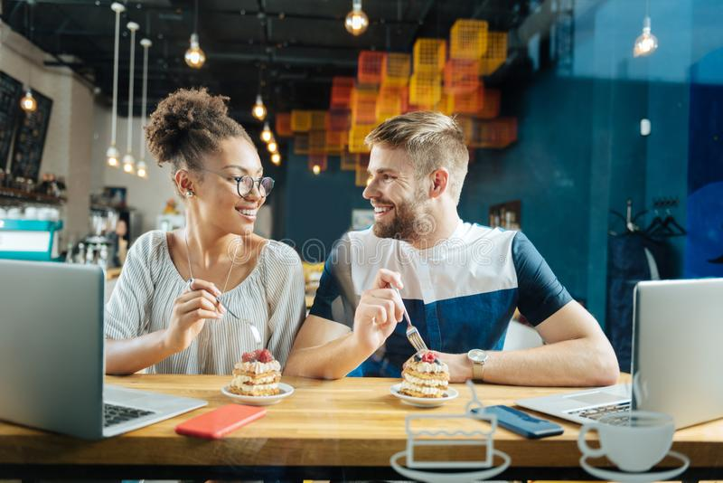 Cute loving couple feeling nice eating some fruit cakes royalty free stock photos