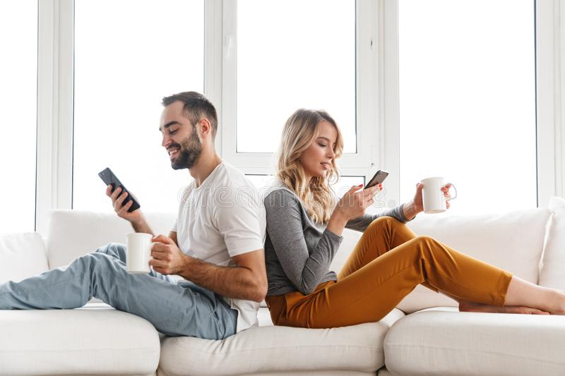 Cute loving couple indoors at home using mobile phones. Image of young cute loving couple indoors at home using mobile phones stock photo