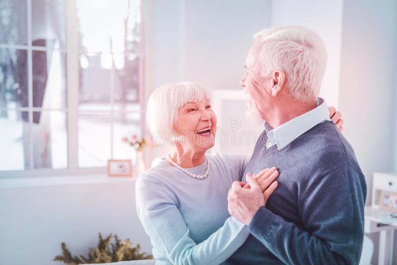 Cute loving couple of pensioners feeling cheerful dancing at home stock photos