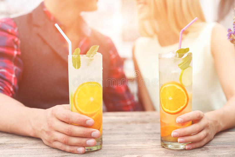 Cute loving couple is resting in cafe. Cheerful men and women are dating in cafeteria. They are talking and smiling. Focus on glasses of cocktail in their hands stock photography