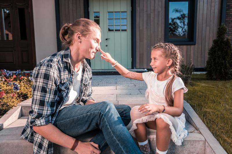 Cute loving daughter touching nose of her handsome blonde-haired father royalty free stock images