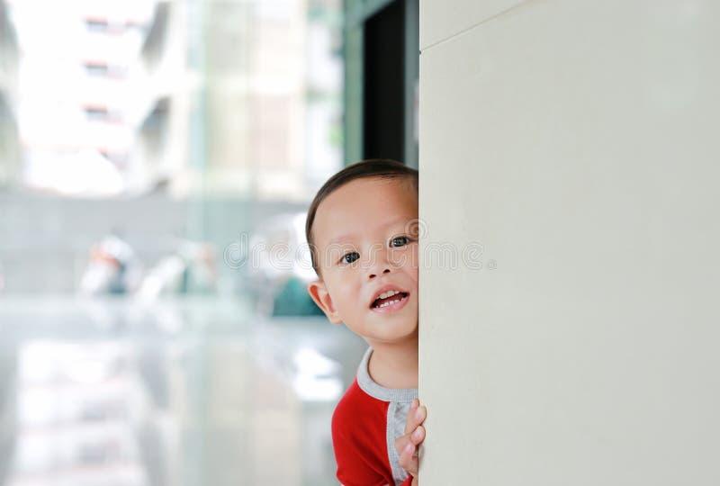 Cute mały chłopiec ukrywa się za pokojem narożnym Dziecko grające w peekaboo gry w środku Co za niespodzianka zdjęcia royalty free