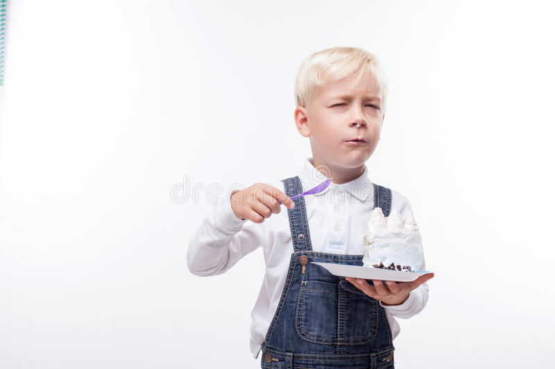 Cute male child is enjoying sweet food. Pretty boy is standing and eating cake greedily. He is holding a plate and spoon. The cake is all over his messy face and royalty free stock photography