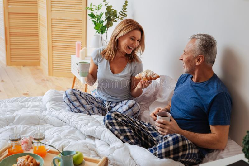 Cute mature couple wearing nice pajamas having breakfast in bed stock photography