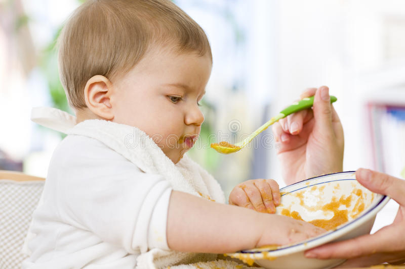Cute messy baby boy playing with food while eating. royalty free stock photos