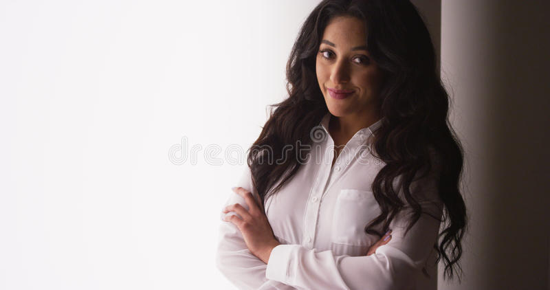 Cute Mexican businesswoman smiling by window royalty free stock image