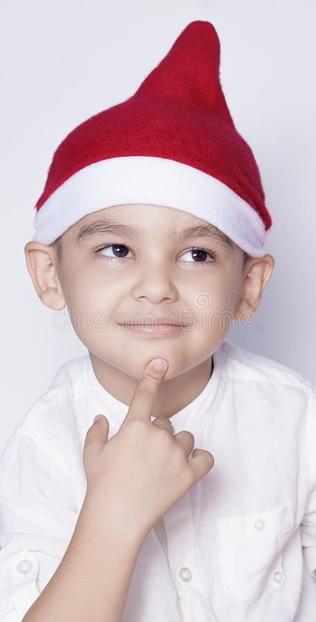 Handsome kid with Santa cap wishing or dreaming something. Child dreaming about Christmas gift. Kid looking up and thinking stock images
