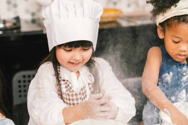 Cute mixed race and African American kid girls baking or cooking together in home kitchen royalty free stock photo