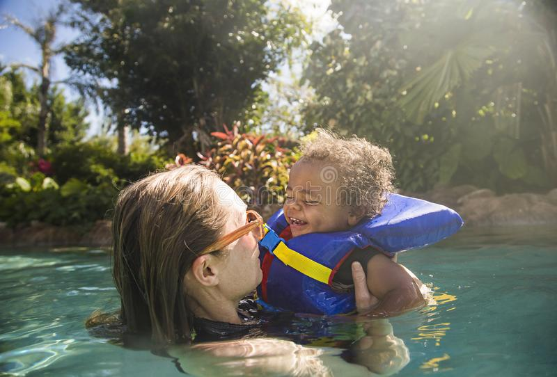 Cute mixed race little boy playing with his mother at a tropical. Beach resort. Having fun together in a beautiful outdoor pool. Little child with a happy stock photography