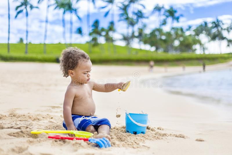 Cute mixed race little boy playing in the sand on a tropical beach vacation. Candid, Full length photo with lots of copy space on a idyllic, scenic beach royalty free stock photography