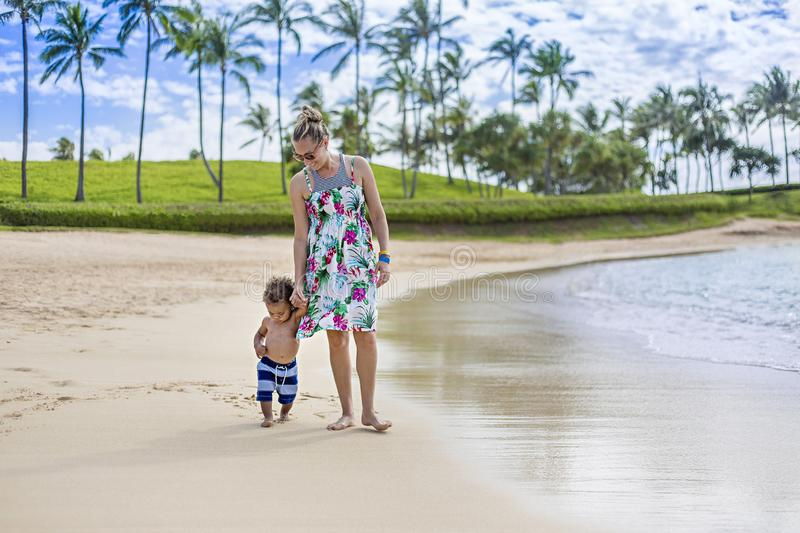 Cute mixed race little boy walking along the beach with his mother on a tropical island vacation. Walking together holding hands making footprints in the sand stock photography