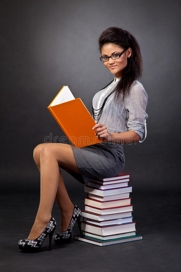 Cute mixed race student girl reading stock image