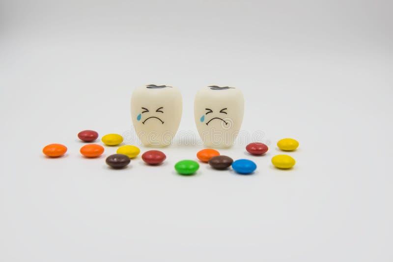 Cute modelo juega los dientes y el caramelo colorido en odontología en un fondo blanco imagen de archivo
