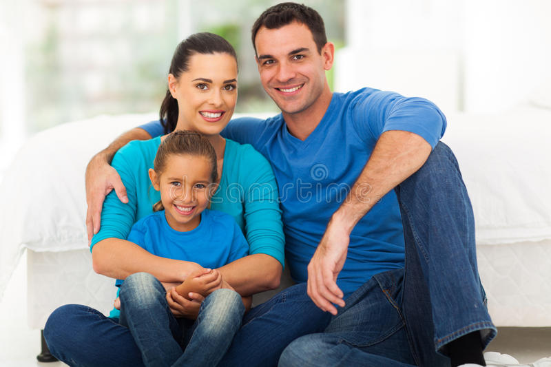 Cute modern family. Of three sitting on bedroom at home royalty free stock image
