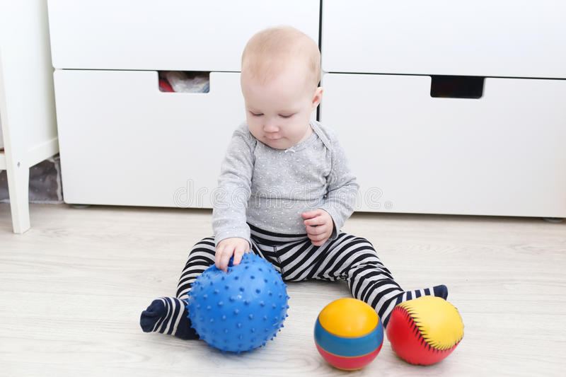 Cute 6 month baby girl plays balls stock image