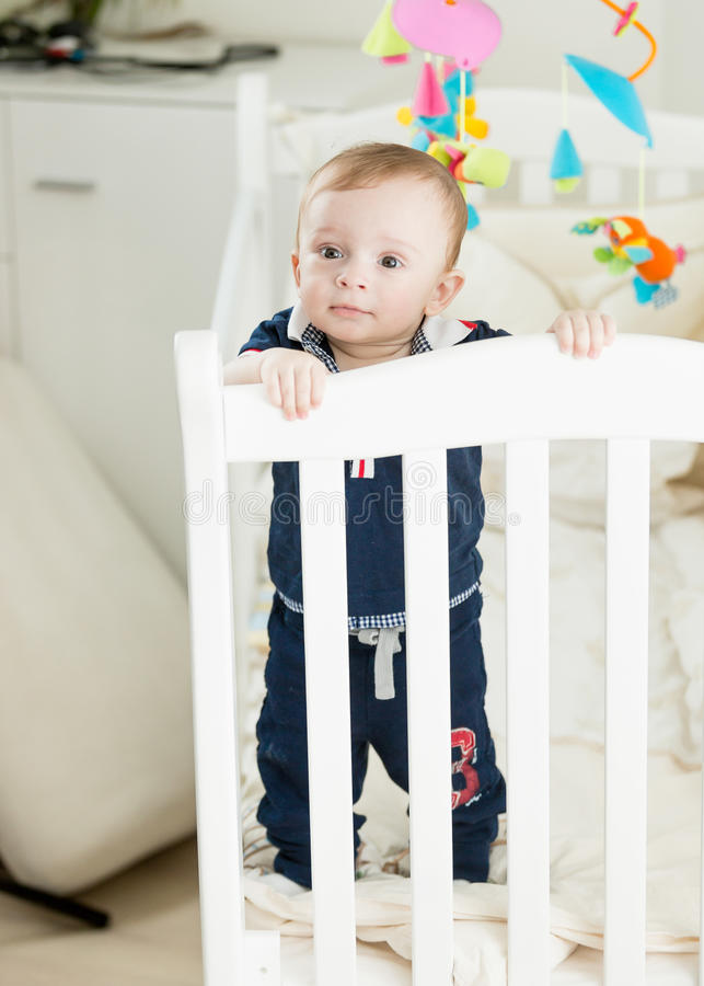 Cute 9 month old boy standing in white wooden crib. Cute 9 month old baby boy standing in white wooden crib royalty free stock image