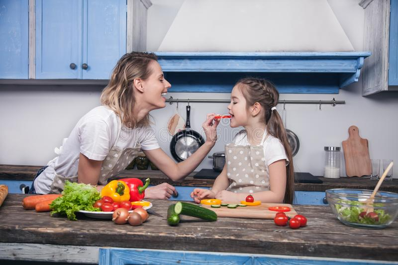 Cute mother gives to her dother a piece of Bulgarian pepper to taste.  stock photography