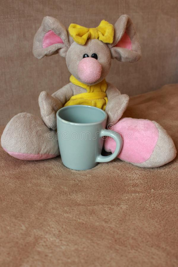 Cute mouse toy with tea cup sitting on sofa. Soft animal toy. Good morning concept. Childhood background. Funny soft mouse toy. Cute mouse toy with tea cup stock photos