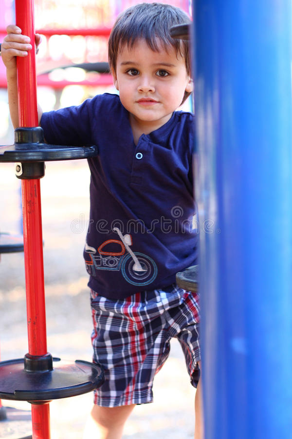Cute multicultural boy at playground stock photos