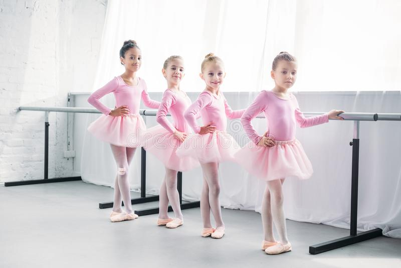 Cute multiethnic kids in pink tutu skirts exercising and smiling at camera. In ballet studio stock image