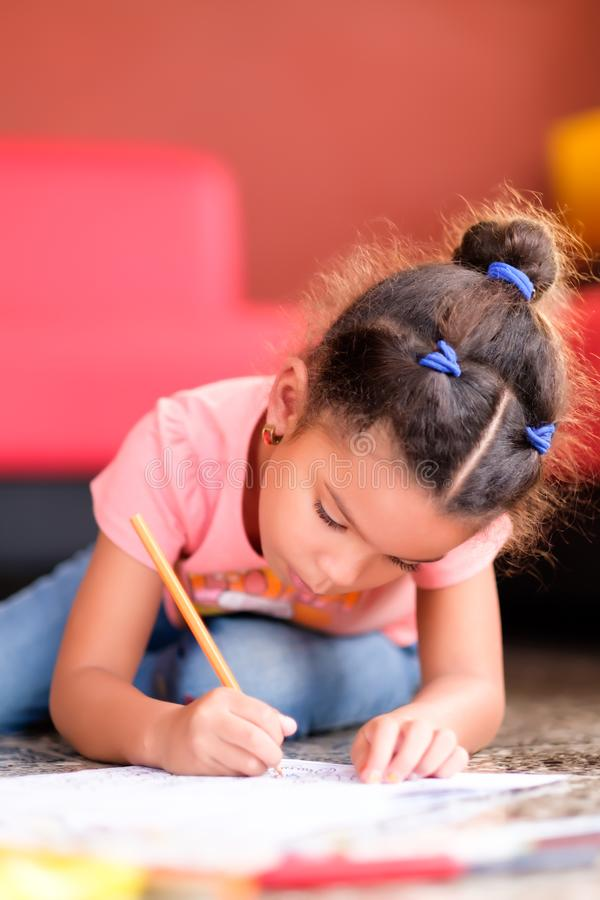 Cute multiracial small girl drawing on a coloring book royalty free stock image