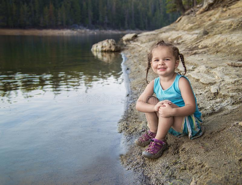 Toddler girl at lake`s edge royalty free stock images