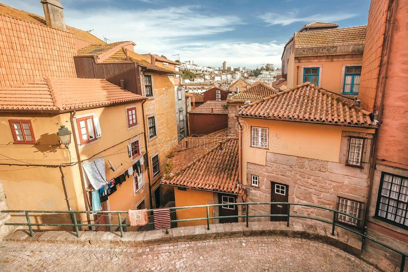 Cute narrow streets with historical houses and red tile roofs of the big Porto city, Portugal.  royalty free stock photo