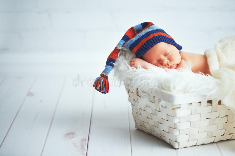 Cute newborn baby in blue knit cap sleeping in basket stock photo