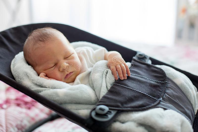 Cute newborn baby boy, sleeping in a swing royalty free stock photos