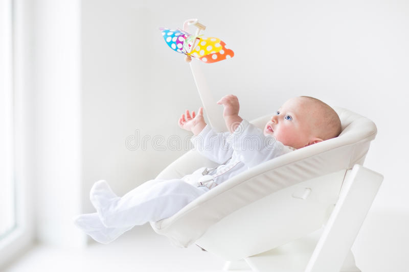 Cute newborn baby boy watching colorful mobile toy stock images