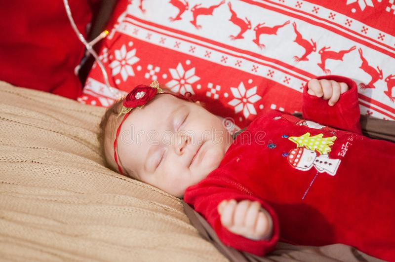 Cute newborn baby in a Christmas costume on a bed at home royalty free stock images