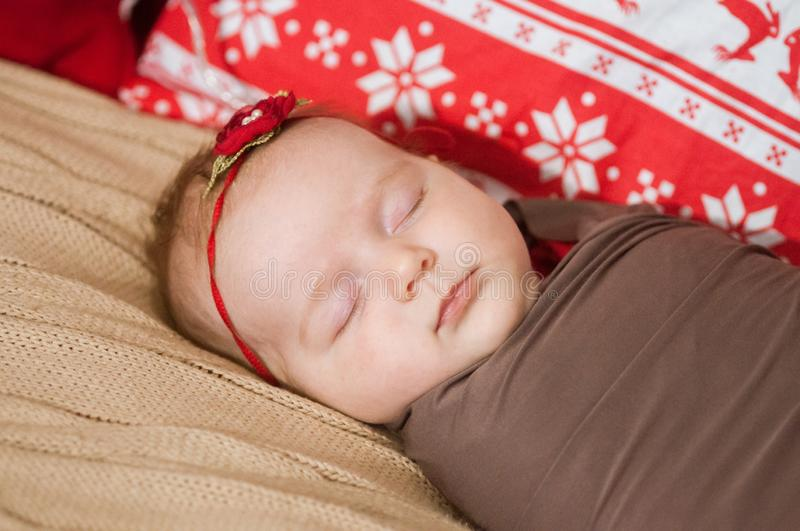 Cute newborn baby in a Christmas costume on a wooden bed royalty free stock photography