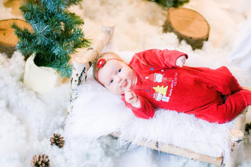 Cute newborn baby in a Christmas costume on a wooden bed royalty free stock image