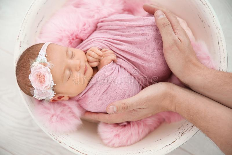 Cute newborn baby girl with her father on light background stock photos