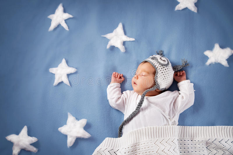 Cute newborn baby girl lying in the bed. 2 month old child in owl hat sleeping on blue blanket royalty free stock photography