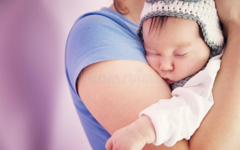 Cute newborn baby girl sleeping. Woman holding infant child royalty free stock photography