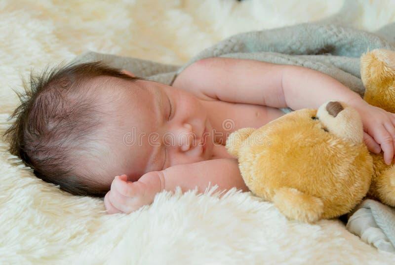 newborn baby girl sleeps with a toy teddy bear stock photo