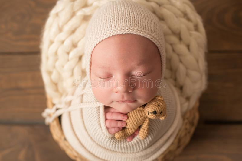 Cute newborn baby in a  knitted hat in a wooden basket  and with a little bear toy. Cute newborn baby in a  knitted hat in a wooden basket in a white blanket royalty free stock photography