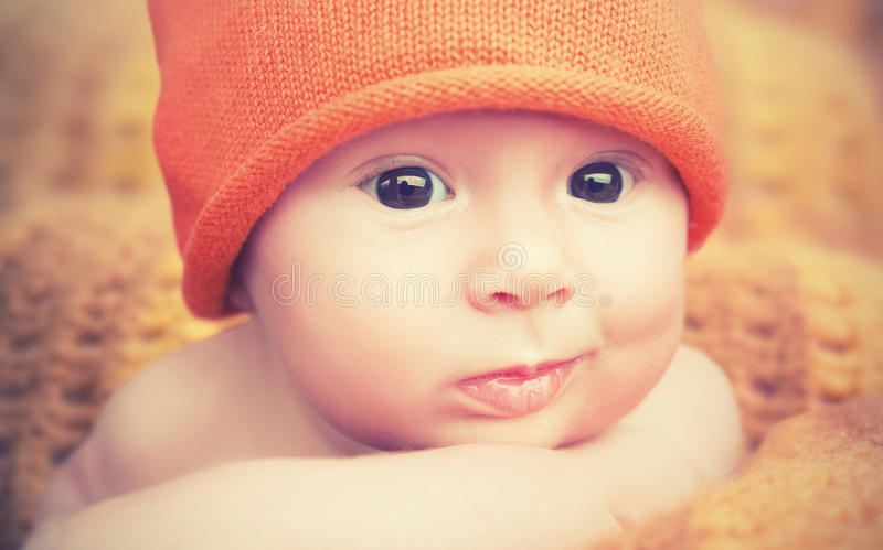 Cute newborn baby in knitted orange hat cap stock photography