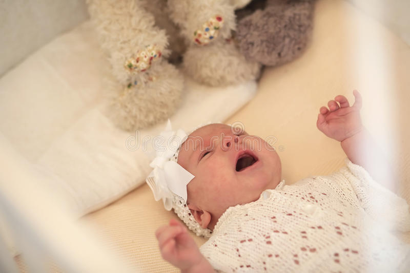 Cute newborn baby lies in the crib and looking mother stock images