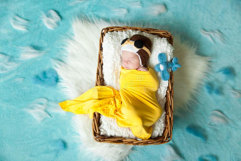 Cute newborn baby in pilot`s hat. Sleeping newborn baby in pilot`s hat in a yellow wrap with felted toy airplane royalty free stock photos
