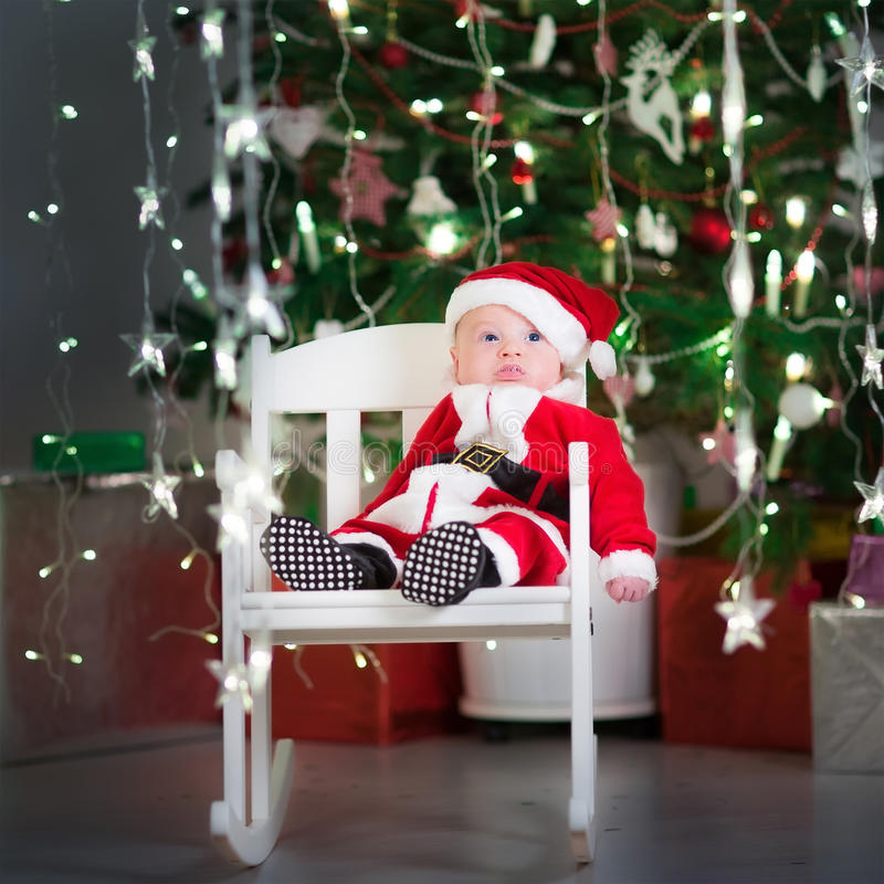 Cute newborn baby in a santa costume and hat sitting under Christmas tree royalty free stock photos