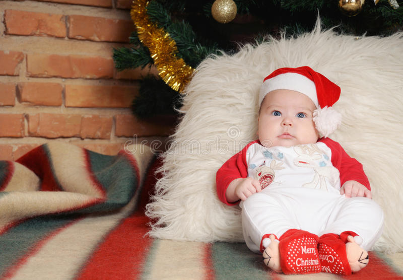 Cute newborn baby in Santa hat sitting near Christmas tree royalty free stock images