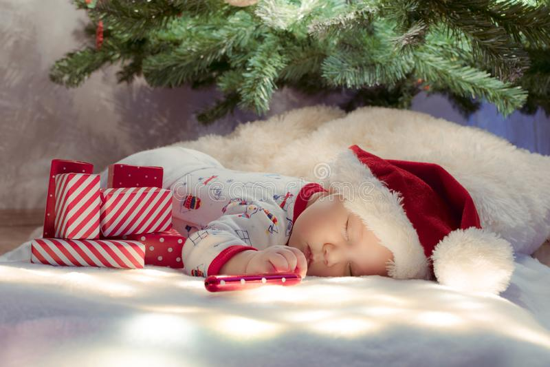Cute newborn baby sleeping under Christmas tree near red gifts wearing Santa Claus hat stock photos