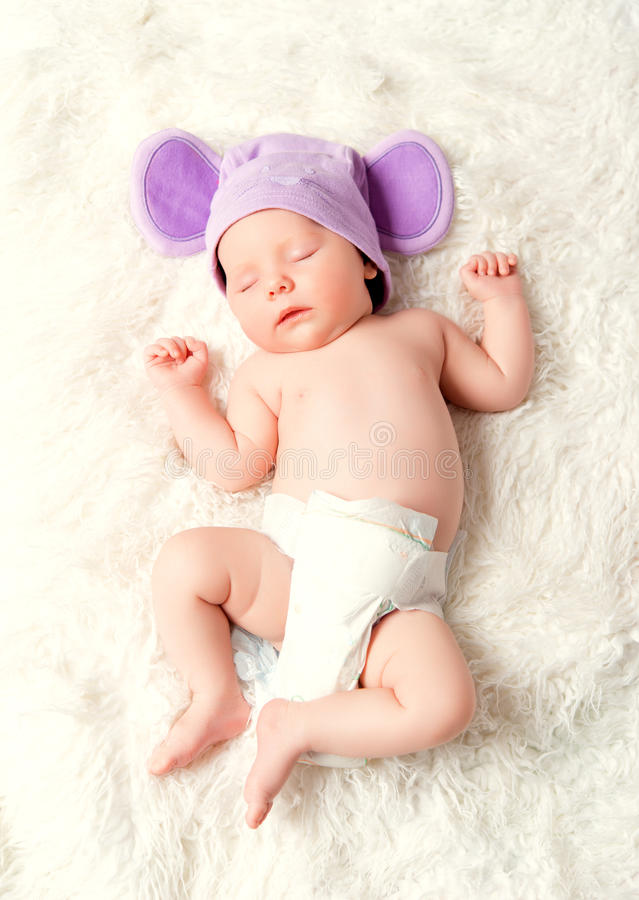 Cute newborn baby sleeps in a hat with ears stock photo