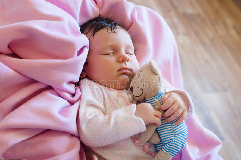 Cute newborn baby sleeps with a toy teddy bear royalty free stock image