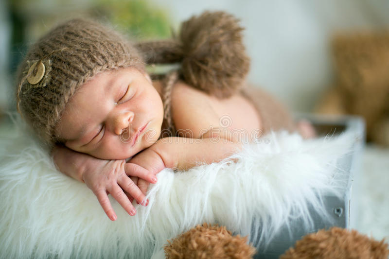 Cute newborn baby sleeps with a toys royalty free stock photos