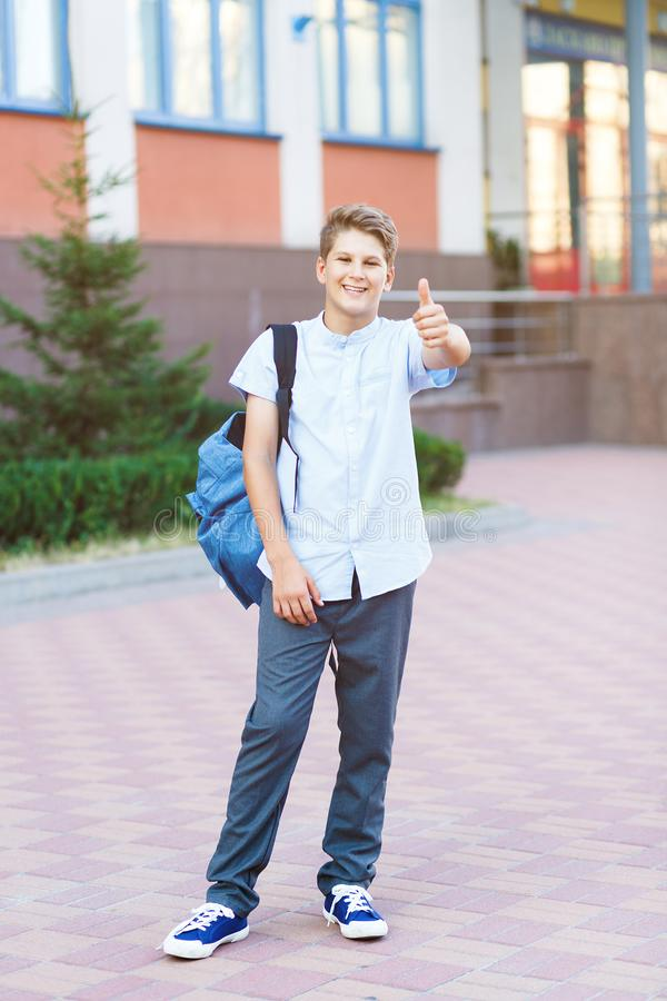 Cute, nice, young 11 years old boy in blue shirt stands with workbooks and backpack in front of his school. Education,. Back to school concept stock photos