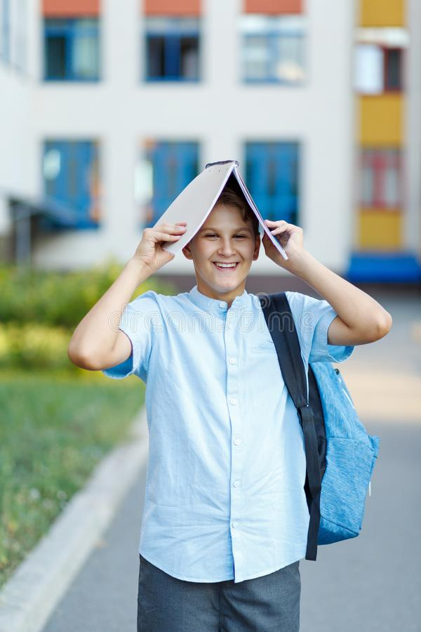 Cute, nice, young 11 years old boy in blue shirt stands with workbooks and backpack in front of his school. Education. Back to school concept royalty free stock photo